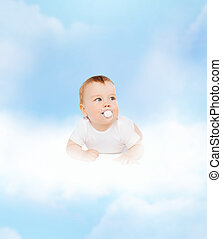 smiling baby lying on cloud with dummy in mouth