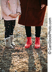 Child and woman feet are in boots in the forest.
