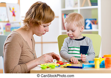 Child and woman play colorful clay toy in nursery