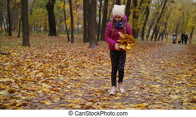 Child arranging bouquet of fallen maple leaves - Cheerful...