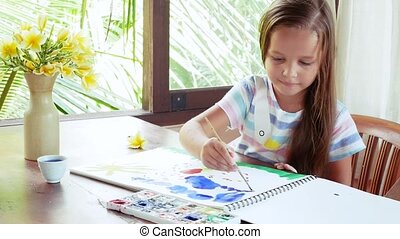 Child artist painting watercolor paints. Girl in her light...