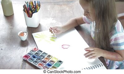 Child artist painting watercolor paints in her light room