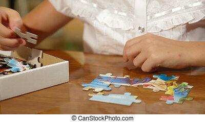 Child Assemble Jigsaw Puzzle - Little girl assemble jigsaw...