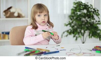 Child at a table looking at camera