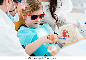Child at dentist office looking after teeth of pet toy, the...