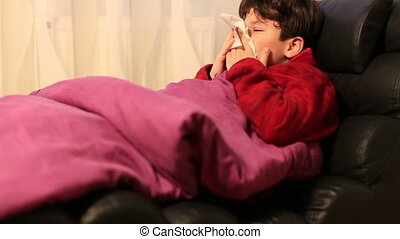 Child at home sick with flu lying on bed and resting