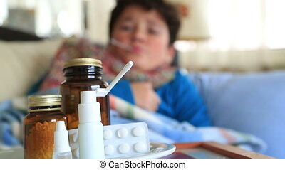 Child at home sick with flu, taking his temmperature