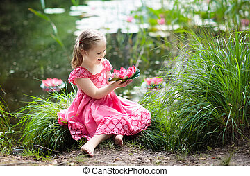 Child at lake with water lily flowers.