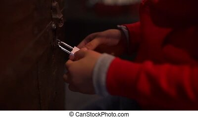 close-up of a childs hands, at night trying to open a combination lock on a chest
