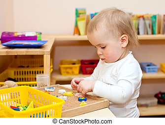 Child at nursery - Little baby girl playing with wooden toys...