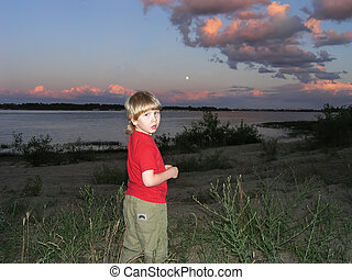child at sunset by the river - A boy stands near the river...