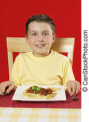 Child at table with plate of food