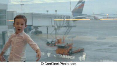 Child at the airport pretending to be a plane - Boy showing...