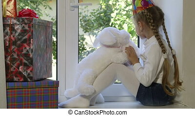 Child awaiting guests looking out the window on her birthday