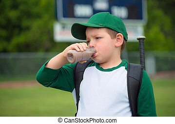 Child baseball player drinking chocolate milk after game