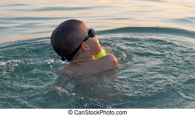 Child bathing in the sea and having fun with ball