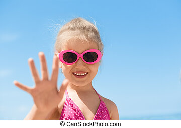 child beach waving hand summer camp