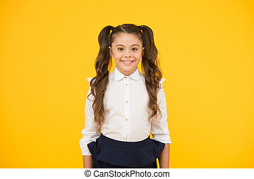 Child beginning a new school year. Adorable small child with long brunette hair wearing formal school uniform. Happy female child back to school. Cute little child smiling on yellow background