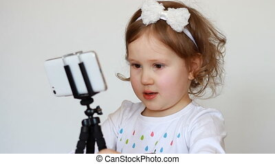 Child bloger recording video on the smartphone.