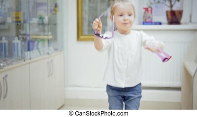 Child - blonde Girl dancing and asks mommy to buy colorful glasses in medical store - shopping in clinic
