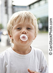 Child blowing a bubble gum on a blurred background