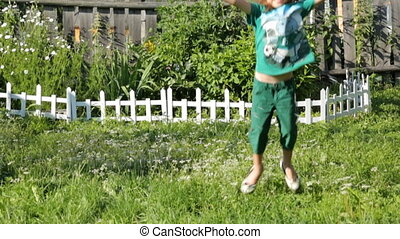 Child blowing soap bubbles in the garden