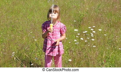 Child blowing soap bubbles on camomile field in summer...