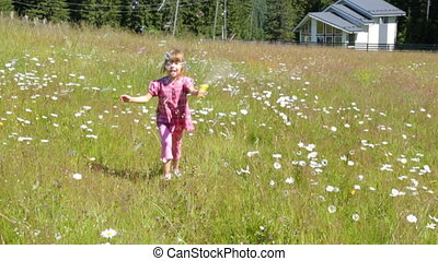 Child blowing soap bubbles on camomile field