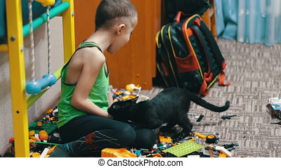 Child Boy and Black Cat Playing with Toys