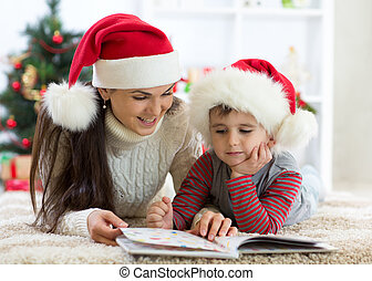 Child boy and his mom reading book at Christmas