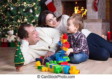 Child boy and his parents playing with block toys under the christmas tree