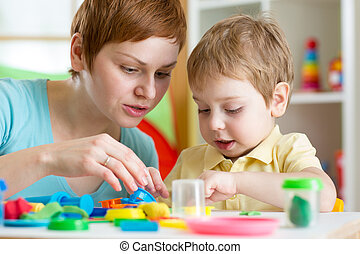 child boy and mother playing colorful clay toy - child boy ...