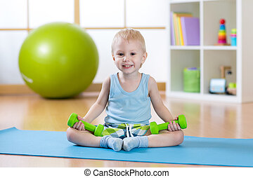 Smiling funny child boy doing fitness exercises