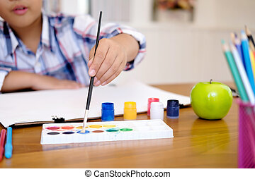 Child boy drawing picture at home.