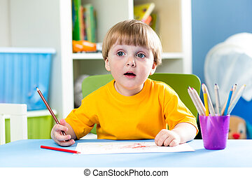 child boy drawing with pencils at table