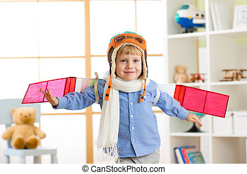 Child boy dressed like a pilot with toy wings playing at home