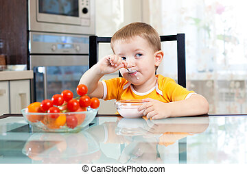 child boy eating healthy food in kitchen