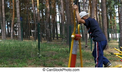 Child boy engaged on Sports Training Equipment at the Street