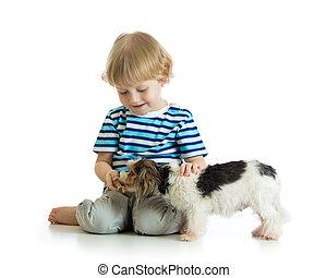 Child boy feeds dog puppy isolated on white