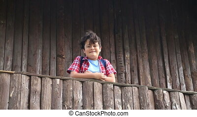 Child boy in a balcony of a wooden house