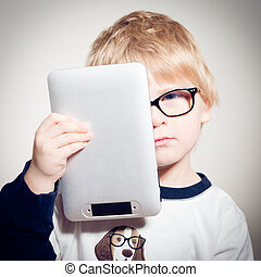 Child boy in glasses holding tablet pc looking & camera -...