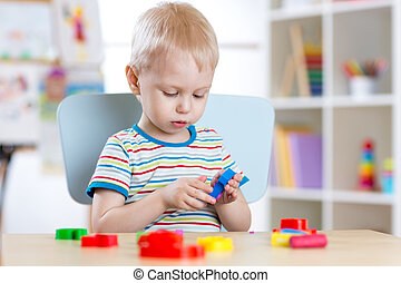 Child boy learning to use colorful play clay in nursery room