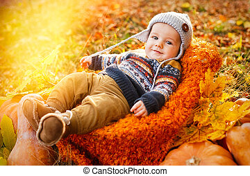 Child boy lies in a basket with pumpkins in autumn leaves.