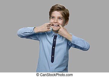 Child boy making funny pulling face with fingers in mouth.