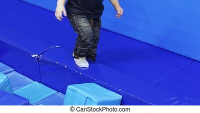 Child boy on the edge of a trampoline balances in an ...