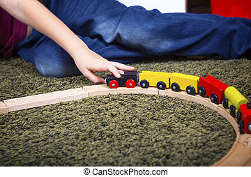 Child boy play with wooden train, build toy railroad at home or daycare.