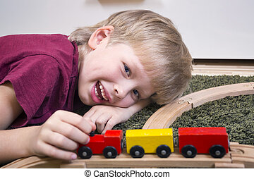 Child boy play with wooden train
