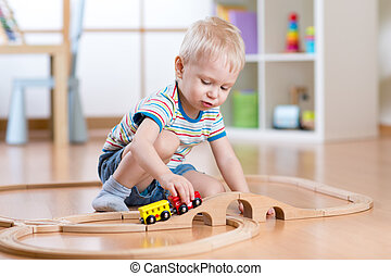Child boy playing in his room with a toy train
