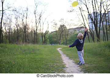 child boy playing park throws flying saucer