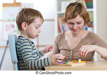 Child boy playing with education toys at the table in kindergarten
